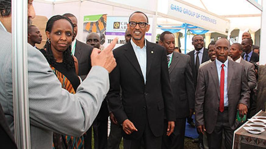 President Kagame and other officials, including Agriculture minister Agnes Kalibata (2L), listen to an exhibitor during  the Second Tea Convention and Exhibition in Kigali yesterda....