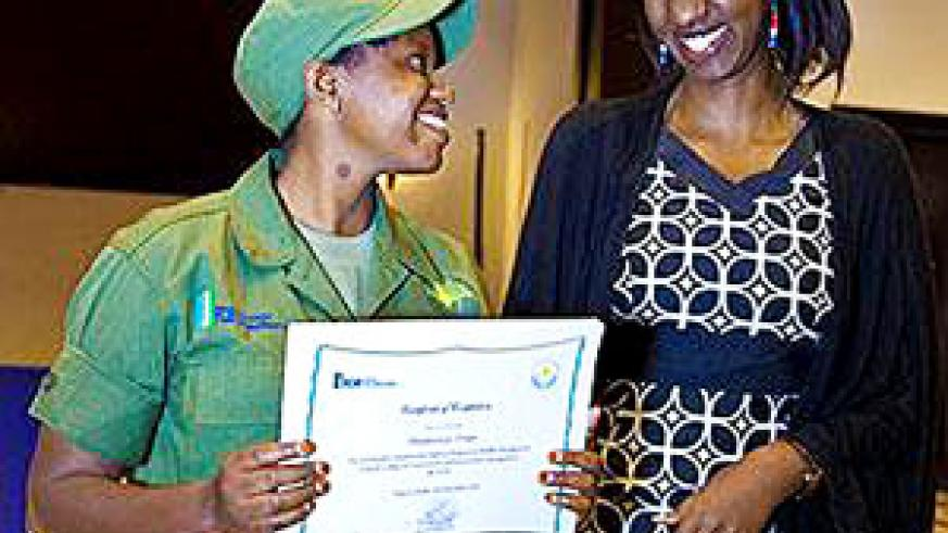 Tourism director Rica Rwigamba (R) awards a student at Kitabi. The New Times/ File.