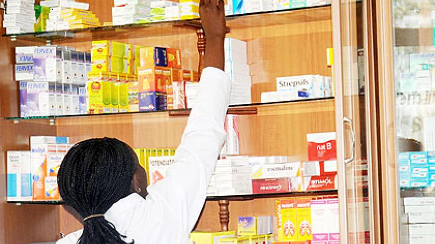 A pharmacist in Kigali selects drugs from the shelf for a patient. The New Times/ File.