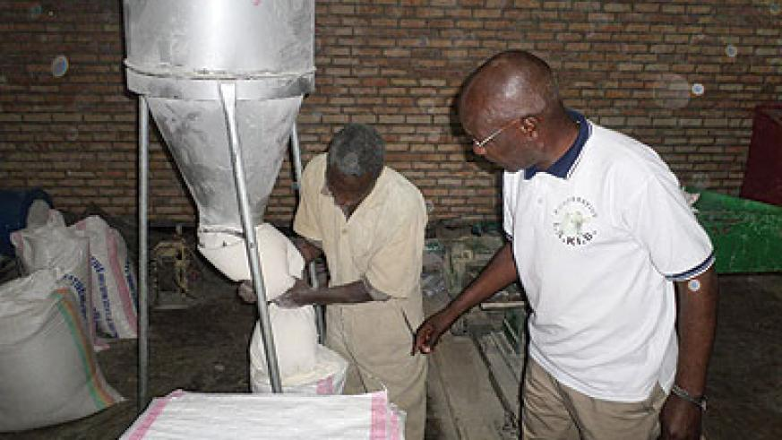 Twine supervises one of the workers at animal feeds processing plant. The New Times / Ivan Ngoboka