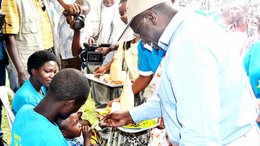 Habumuremyi feeds a child during the launch of the campaign to root out malnutrition on Saturday.  The New Times/ J. Mbonyinshuti.