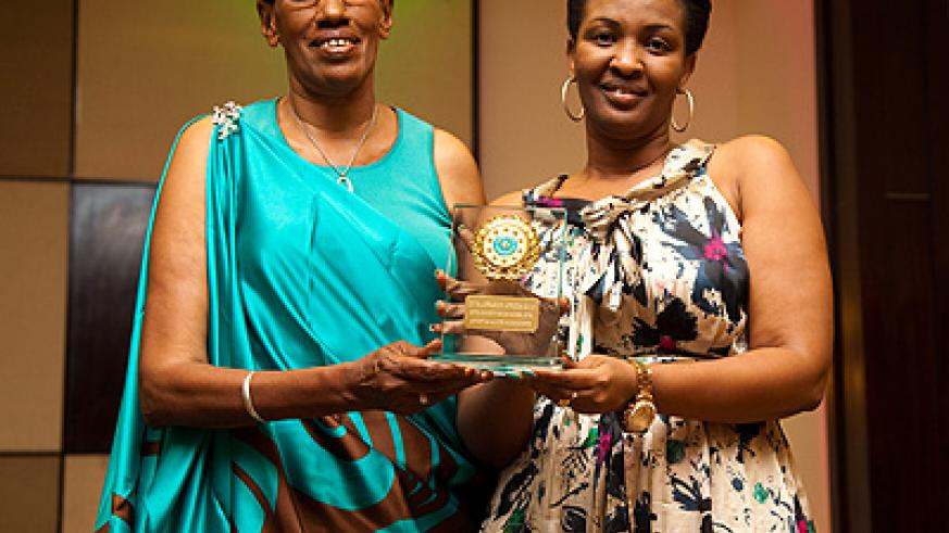 (L-R) Maria Yohana receives the award for best traditional folk diva from Apostle Alice Mignonne Kabera. At the same event, Apostle Kabera was recognised as society role model.