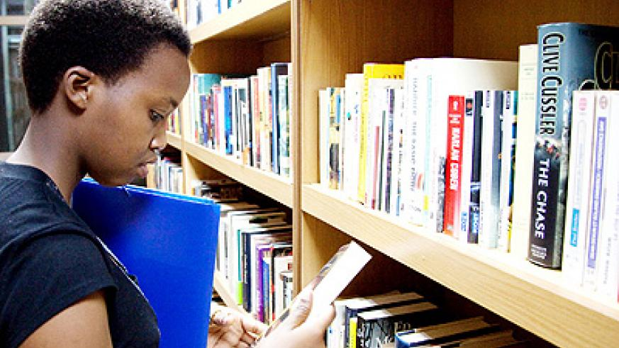 A student searches for books in a Kigali Public Library. The New Times/ File.
