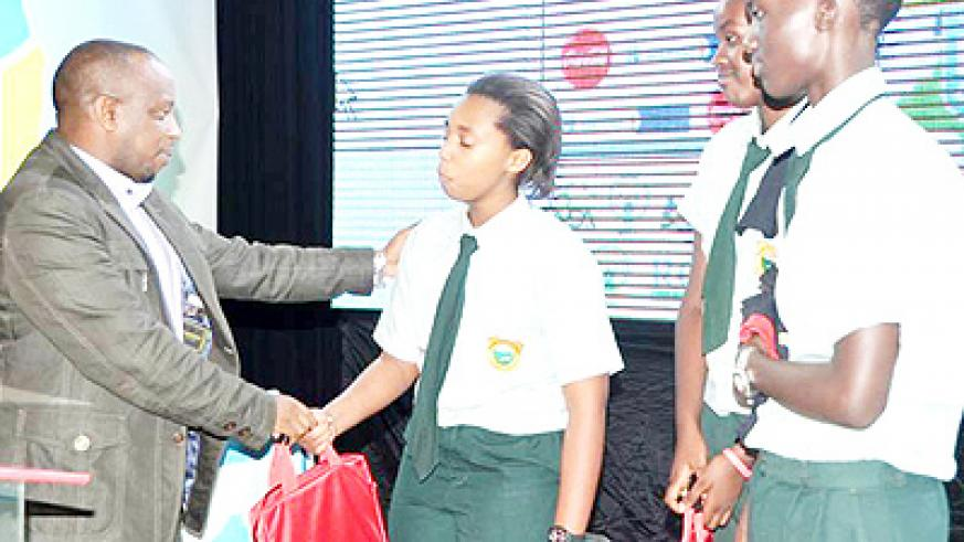 An official from Rwanda Development Board awards a Green Hills Academy debater during the awards ceremony on Sunday.   The New Times/ Courtesy.