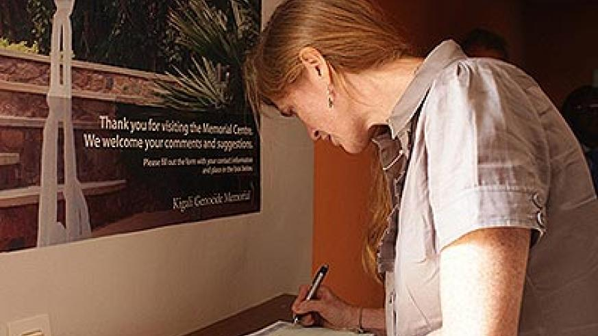"""Amb. Power signs the visitors' book at the Kigali Genocide memorial where she paid a glowing tribute to the people of Rwanda for """"opening up"""" to the rest of the world in the ...."""