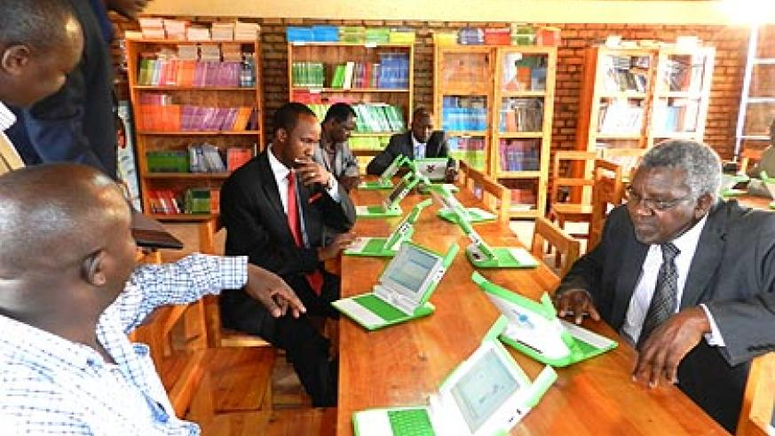 Visiting Kenyan MPs study some of the green and white laptops used by pupils of Gahini Primary School in Kayonza District. The legislators are in the country to understand the one ....