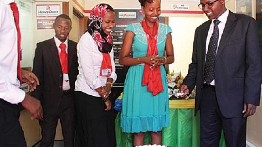 UAE Exchange Rwanda employees and guests cut a cake as the firm launches customer service week. The New Times / Courtesy photo