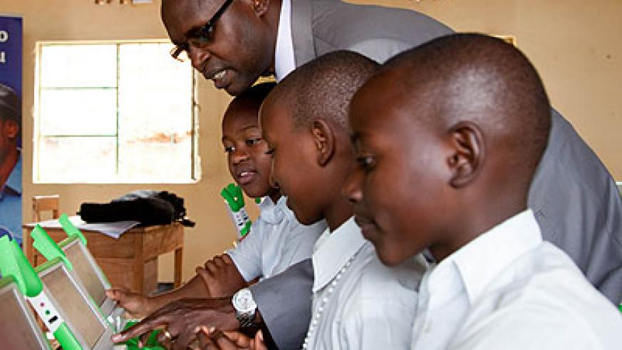 State Minister for Primary and Secondary Education Mathias Harebamungu engage primary school pupils using One Laptop per Child gadgets during a field visit. The New Times/File
