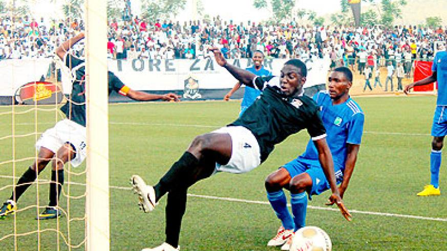 APR defender clears a ball past Espérance striker last weekend in the second match of the Turbo King Football League. The New Times/Courtesy