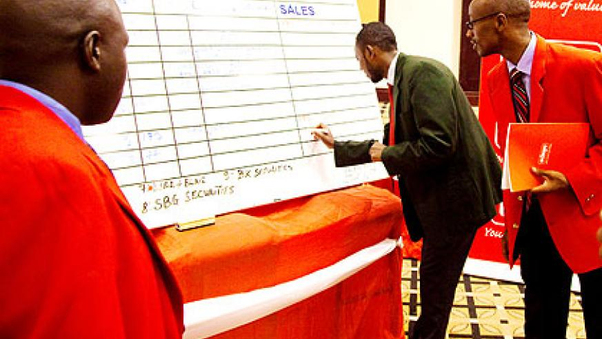 A broker updates a stock trading board in Kigali yesterday. The New Times/  T. Kisambira.