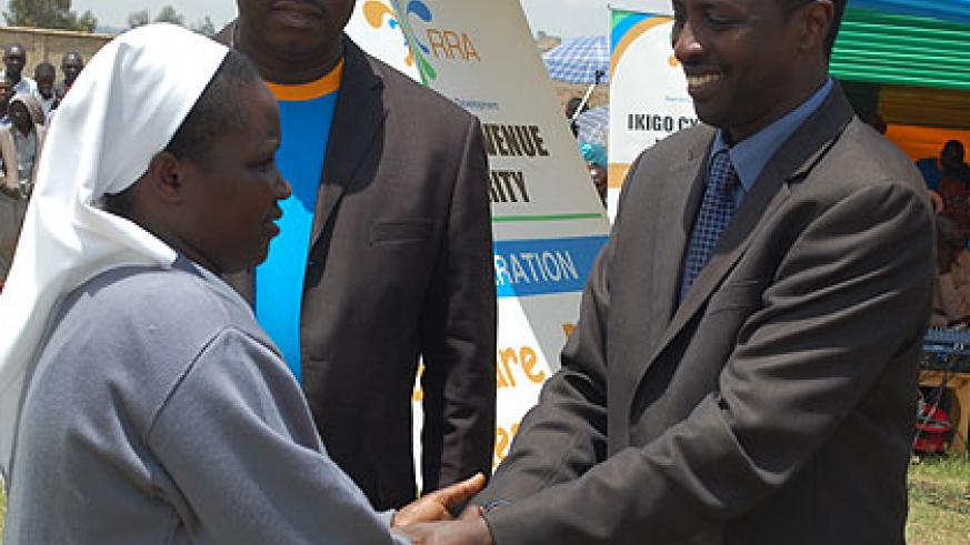 Governor Munyantwari congratulates a representative of Cntre d'Acceuil St Andre Kabgayi which emerged the best taxpayer in the region. Saturday Times/ Jean Pierre Bucyensenge