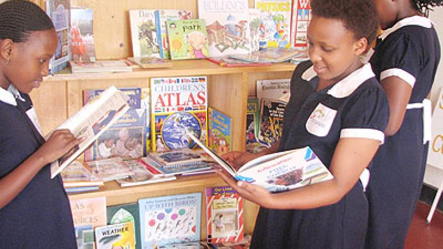 Pupils of Alpha Community Academy check out reading material in their library. The New Times/ Courtesy.