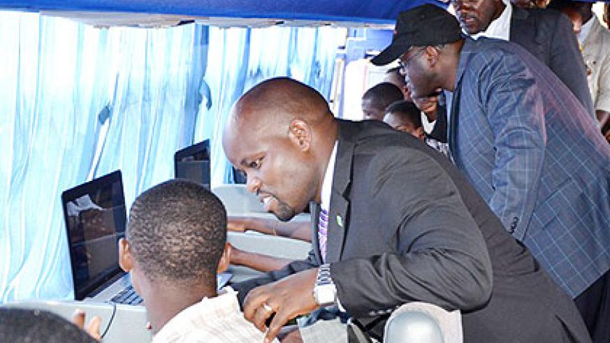 Nsengimana (C) chats with youths at an ICT hub in Kigali. The New Times/ File.