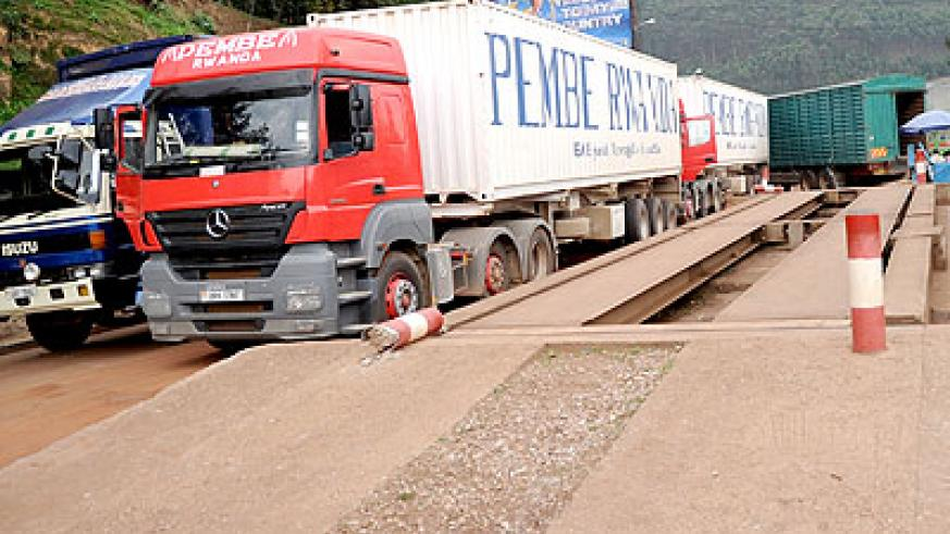 <p>Among some of the resolutions was that all Partner States will comply with the instructions that transit cargo will be weighed once at the point of entry into each member state territory. Above, trucks cross the Rwanda - Uganda border of Gatuna and below flags of the four countries  The New Times/File</p>