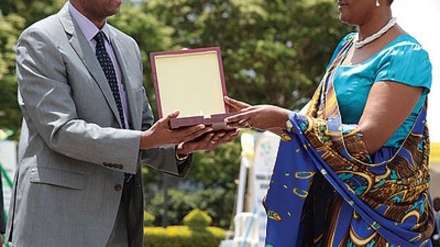 The Speaker of Parliament Donatille Mukabalisa hands over an awards to one of the taxpayers recognised  by RRA on Saturday. Twenty-three firms and individuals were also recognised ....