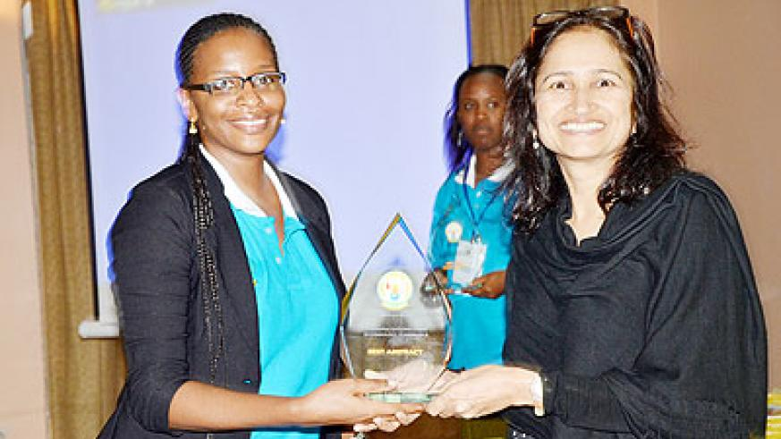 Dr Muhimpundu receives an award at a past conference. The New Times/ Courtesy.