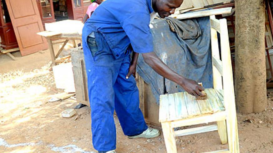 A carpentry student polishing one of his products. Education Times/ Timothy Kisambira.