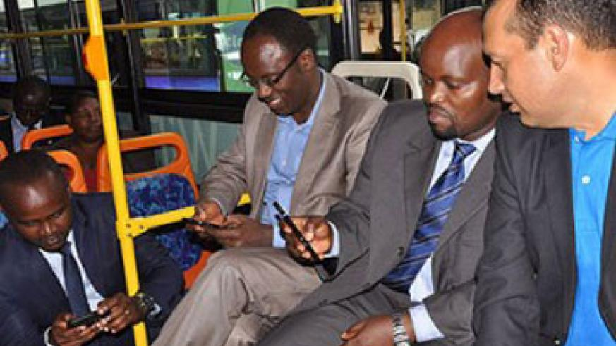 Nsengiyumva (second right) and City of Kigali Mayor Fidel Ndayisaba enjoy free Internet on a city commuter bus during the launch of the 'Smart Kigali' initiative. The New Times / File