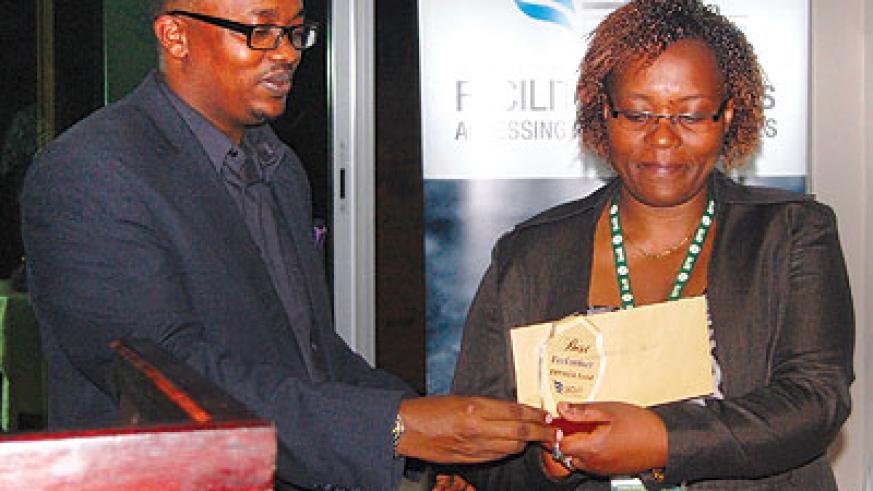 One of the managers receives her award from BDF CEO Innocent Bulindi.  The New Times / Ben Gasore