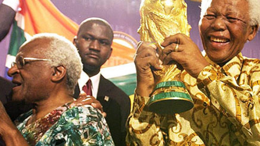 Nelson Mandela lifts the World Cup Trophy after playing a crucial role in winning South Africa the rights to host the 2010 finals. Left is his anti-Apartheid struggle colleague archbishop Desmond Tutu. Net photo.