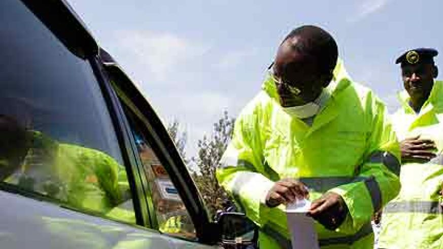 Ndayisaba explains to a driver the meaning of a road safety sticker before placing it on his car. The New Times/ T.Kisambira.