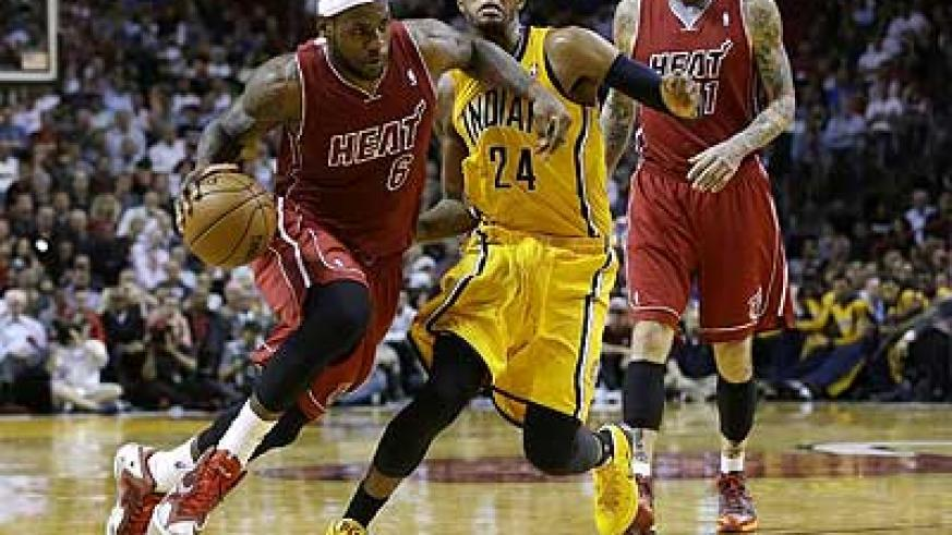 Miami Heat's LeBron James (L) drives to the basket past Indiana Pacers' Paul George during the second half of an NBA basketball game, Wednesday, December 18. Net photo.