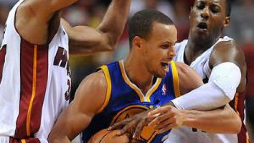 Golden State Warriors point guard Stephen Curry (C) is fouled by Miami Heat point guard Mario Chalmers (R) as small forward Shane Battier (L) defends the play during the second hal....