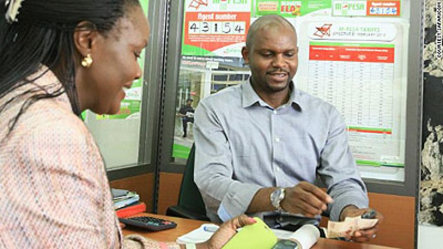 A Safaricom M-Pesa dealer serves a customer. The telecom firm controls over 80 per cent of the Kenya market.  Net photo