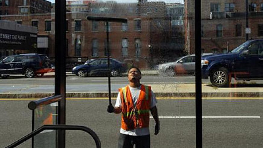A worker washes the windows of a silver line bus station in Boston, Massachusetts.