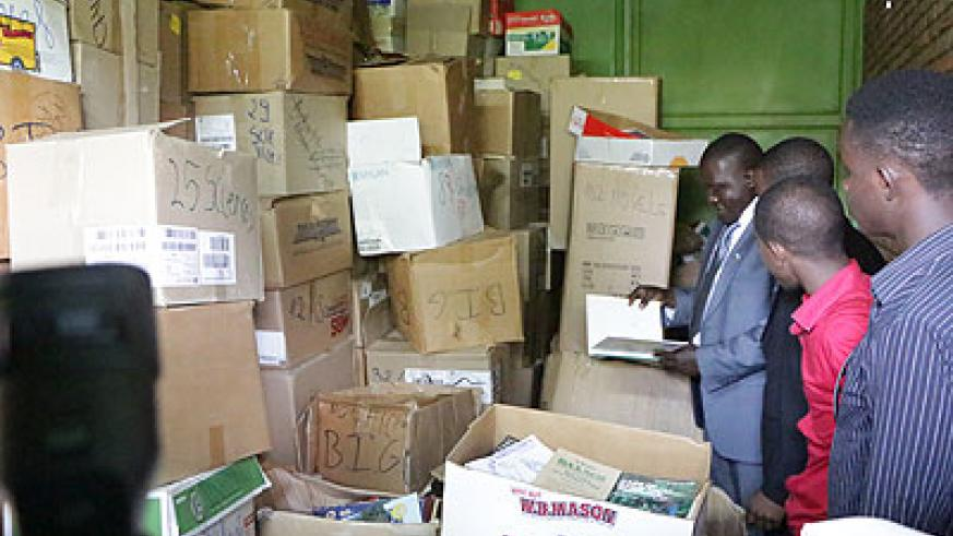 Isaro Foundation officials inspect a consignment of books. Education Times / Susan Babijja.