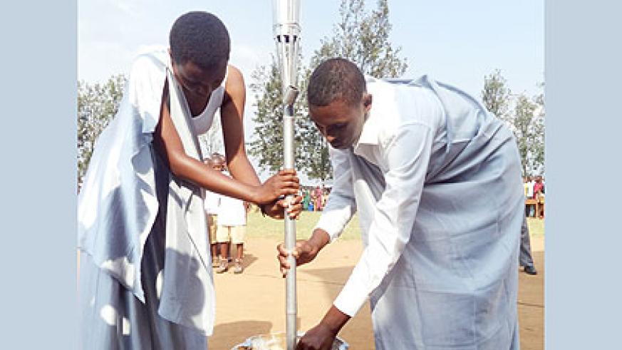 <p>The youth who received the Kwibuka Flame in Mugina Sector anchor it in a vase ahead of the ceremony yesterday. Kamonyi residents expressed determination to strive for prosperity as they received the Flame that many called the &ldquo;messenger of hope.&rdquo; The New Times/ Jean Pierre Bucyensenge.</p>