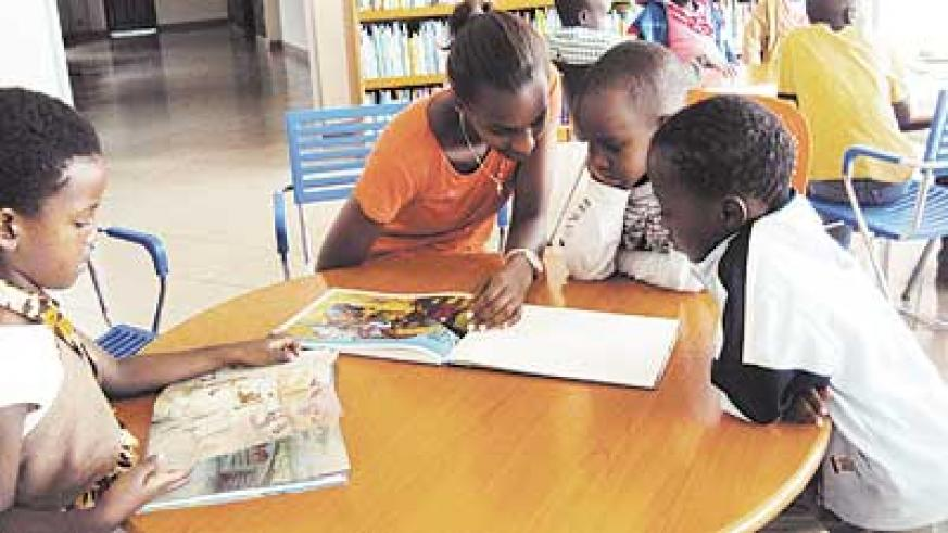 A volunteer helps children to read at the National Library in Kacyiru. Education Times/File Photo