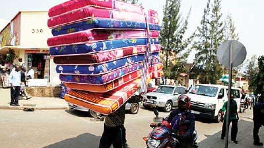 A casual labourer carries mattresses at downtown in Kigali. The New Times/ T.Kisambira.
