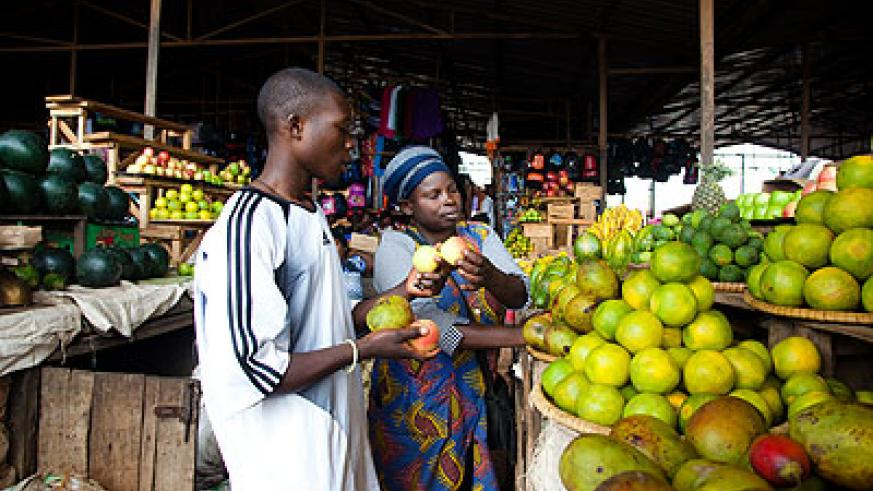 A woman sells friuts in Kicukiro market. Experts have called for more support to the private sector.  The New Times/ T. Kisambira.