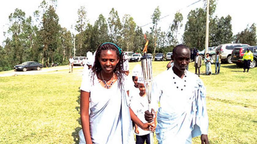 Students aged 20, carry the Kwibuka Flame in Kinazi, Ruhango, on Sunday.  The Flame continues its nationwide tour ahead of the 20th anniversary of the 1994 Genocide against the Tutsi. The New Times/ Jean Pierre Bucyensenge.