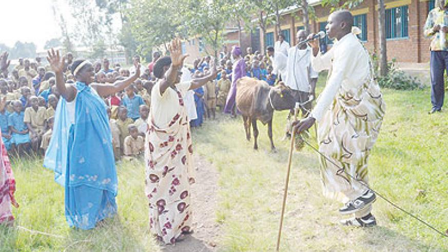 Some of the teachers who received cows for their excellent performance. Right is a man in traditional cloth singing a song  traditionally dedicated to cows. The New Times/T. Kisambira