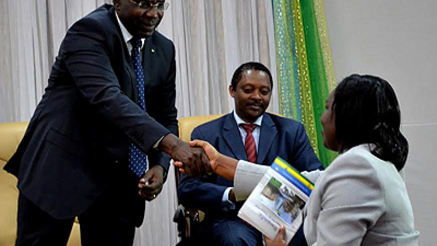 Habumuremyi (left) handing over his book to minister Venantie Tugireyezu at the launch last week. /Education Times/Faustine Niyigena