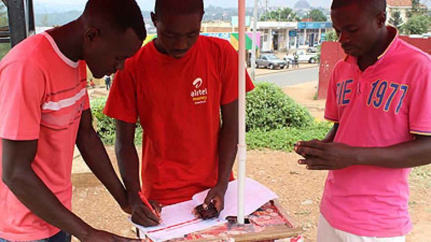 Niyikora (centre) serves a customer. The enterprising youth has been able to fund his education using savings from airtime and airtel money agency sales. The New Times / Ben Gasore