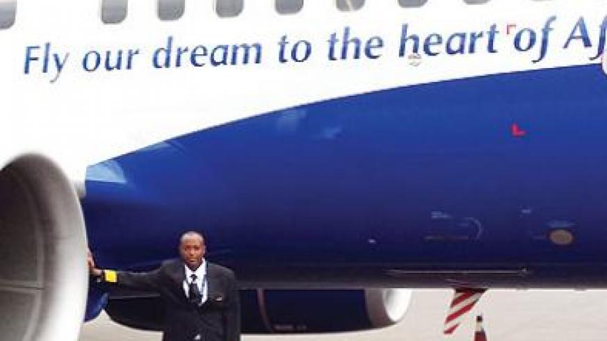Murabukirwa stands next to a RwandAir plane. He became the first Rwandan national pilot to put on a four- striped pilot jacket.