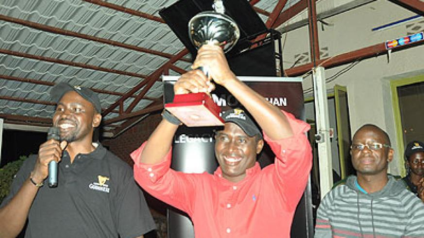 Kigali Golf club president Dr. Richard Gakuba recieves the rotating trophy from his counterpart at Entebbe Golf club Oscar Semawere (R) on Saturday. Times Sport / Courtesy.