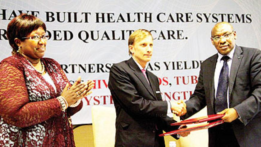 Finance minister Amb. Claver Gatete (R) shakes hands with Global Fund Executive Director Mark Dybul as Health minister Dr Agnes Binagwaho looks on. John Mbanda.