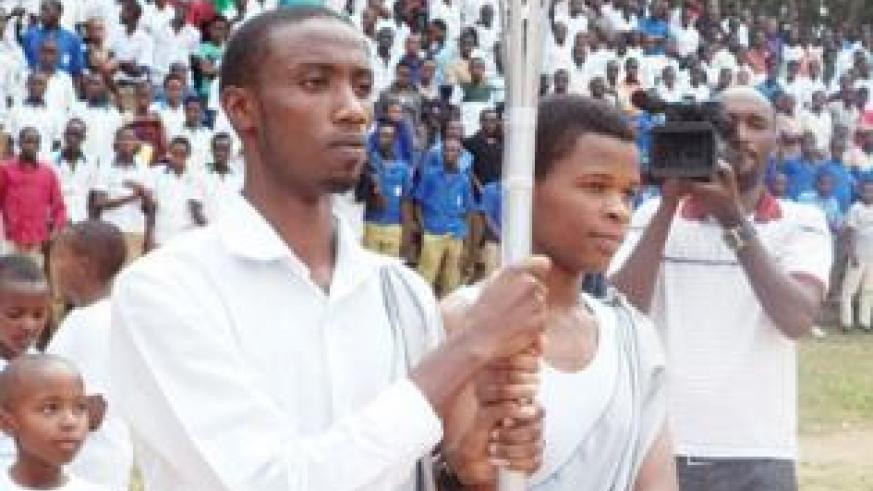 Muhanga students, Jean-Marie Vianney Uwishema  and Jacqueline Niyonsenga received the Flame as it arrived in Muhanga on Thursday.    Jean Pierre Bucyensenge.