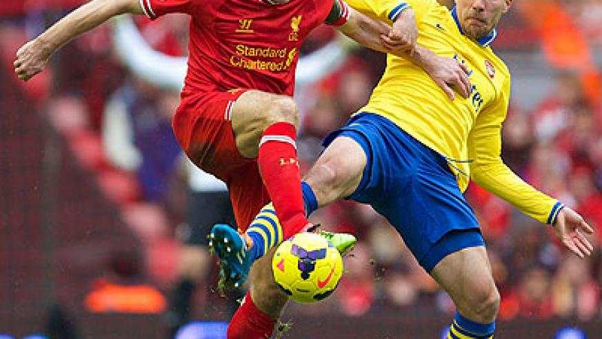 Liverpool's captain Steven Gerard nips the ball away from Arsenal striker Lucas Podolski during last weekend' Premier League encounter at Anfield. Net photo