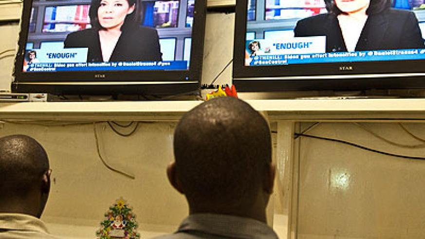 People watch news at one of the Pay TV firm outlets in town. File.