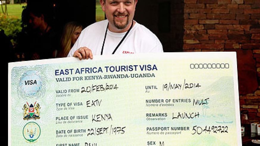 A tourist shows off a dummy East African Tourist Visa at the Heads of State summit in Kampala, yesterday. Courtesy.