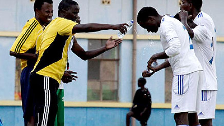 Camarade Banamwana (left) pours water on one of his players during a previous league game against Rayon Sports. File