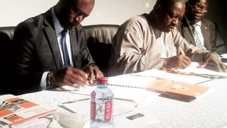 The Rwandan Private Sector Federation chairman, Benjamin Gasamagera (L), and the president of Ghana Chamber of Commerce, Seth Adjei Baah (C), sign the trade agreement in Accra on F....