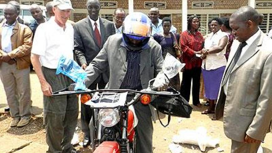 Heifer officials and Eastern Province Executive Secretary Jean Marie Vianney Makombe hand over a motorcycle to a farmer. Stephen Rwembeho