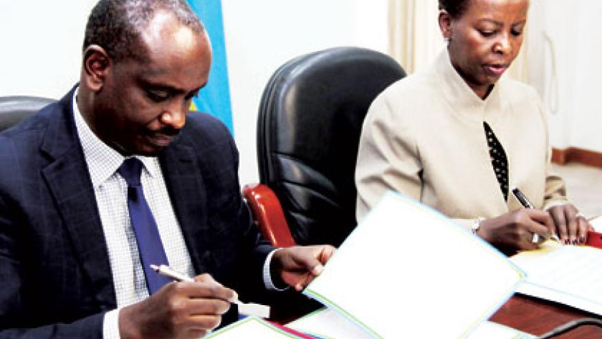 EAC Secretary General, Dr. Richard Sezibera (L), and Foreign Affairs minister, Louise Mushikiwabo, sign an agreement that allows Rwanda to host the EAC Science and Technology Commi....