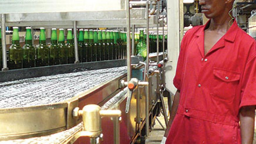 A worker at Bralirwa supervises the production process. Standards body has directed brewers to start using glass bottles like these from May 1. John Mbanda